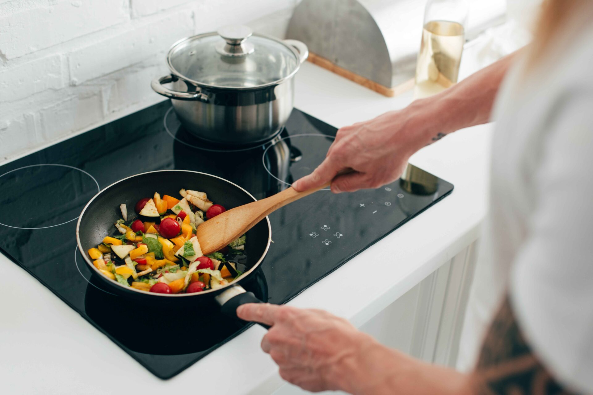 Man cooking vegetables in frying pan on electric