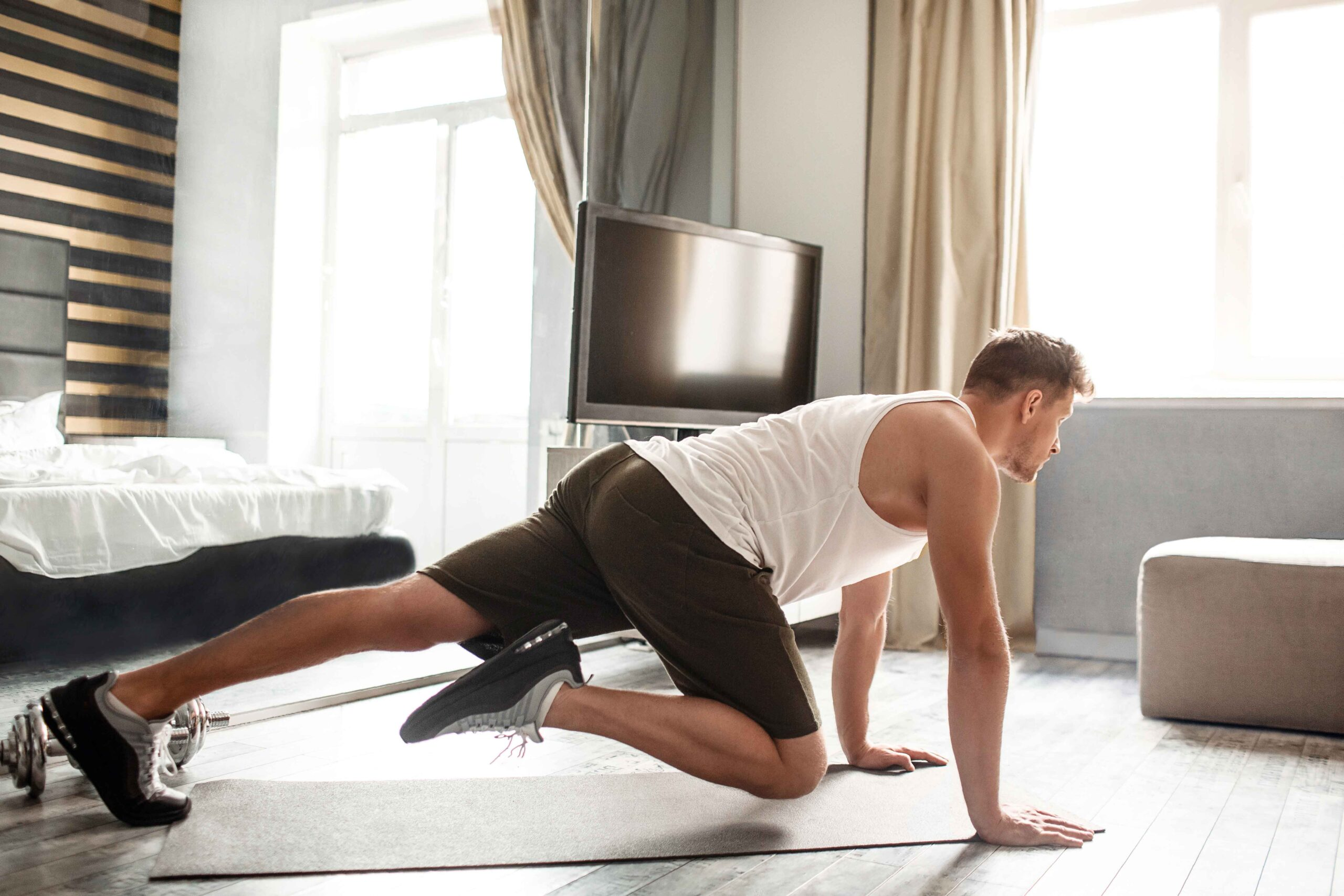 Young well-built man go in for sports in hotel room. He stand on hands and move legs. Guy look straight forward. He exercise alone in room.