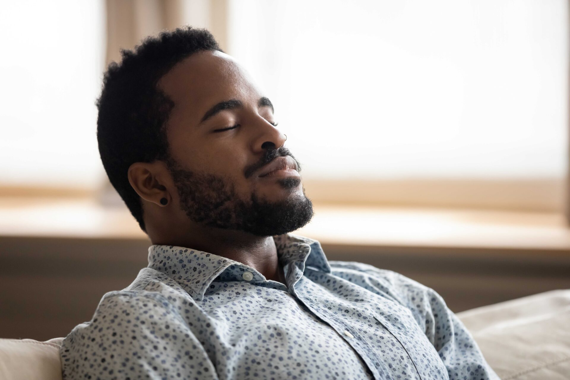 Tranquil young man resting eyes closed breathing on couch