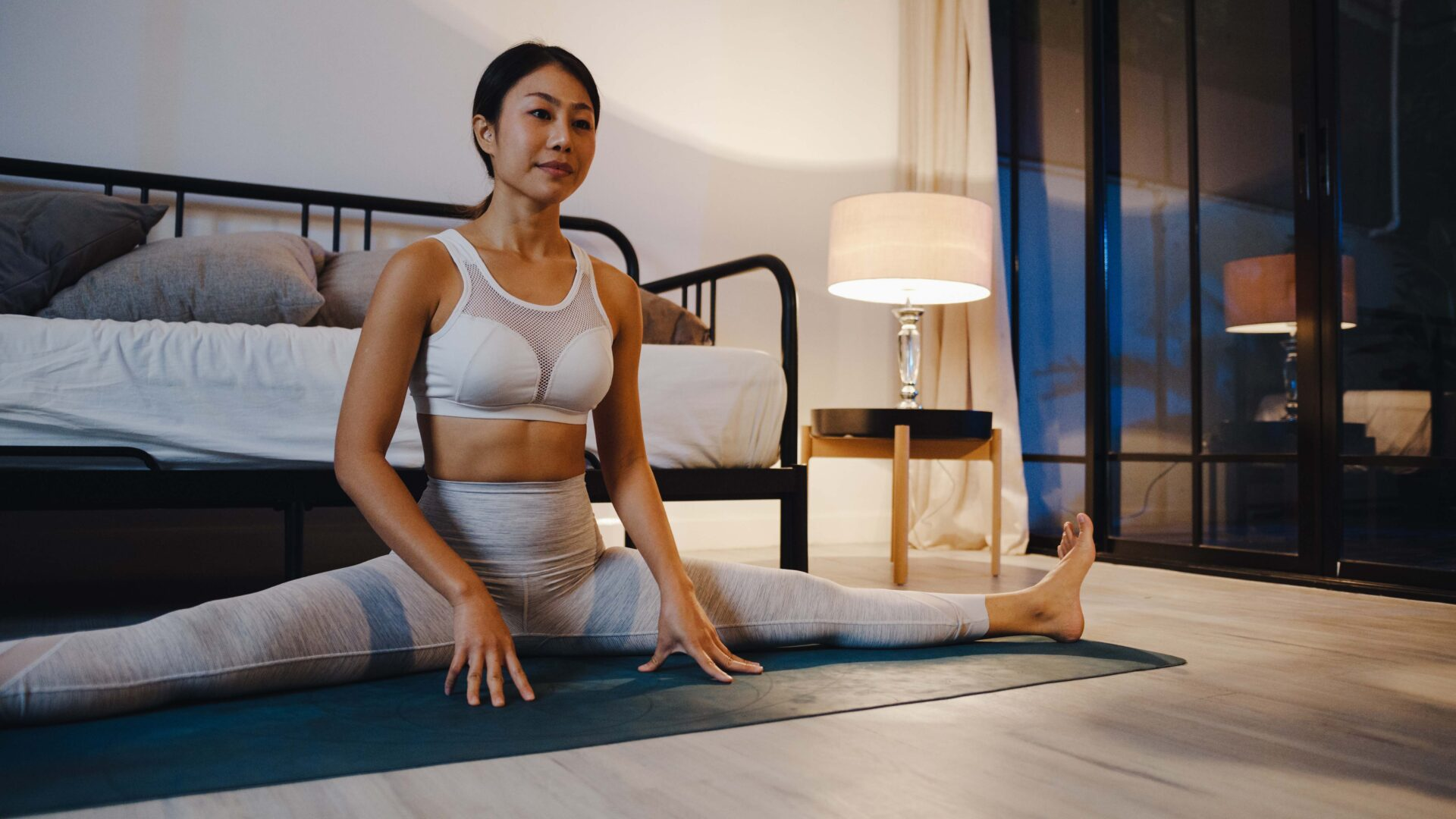 Young lady doing yoga exercise working out in bedroom